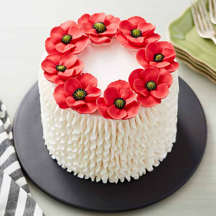 white buttercream frosted cake topped with buttercream poppy flowers
