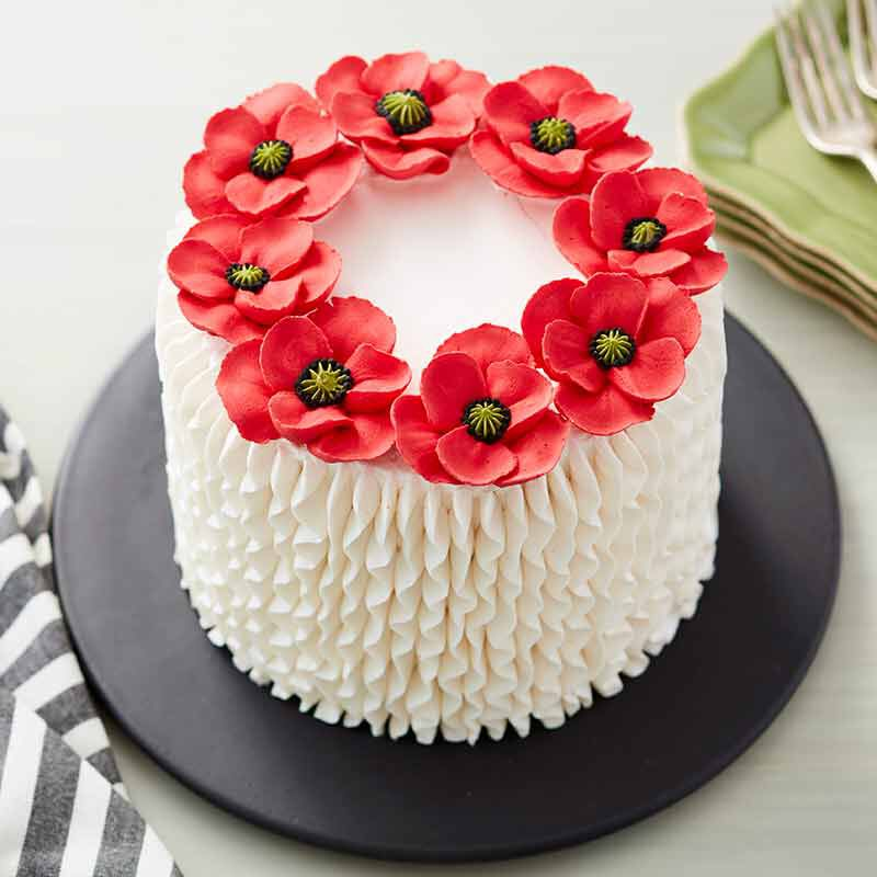white buttercream frosted cake topped with buttercream poppy flowers image number 0