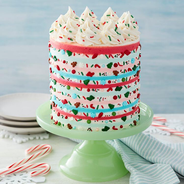 Cake with red, light blue, and white stripes, with Christmas-shaped sprinkles