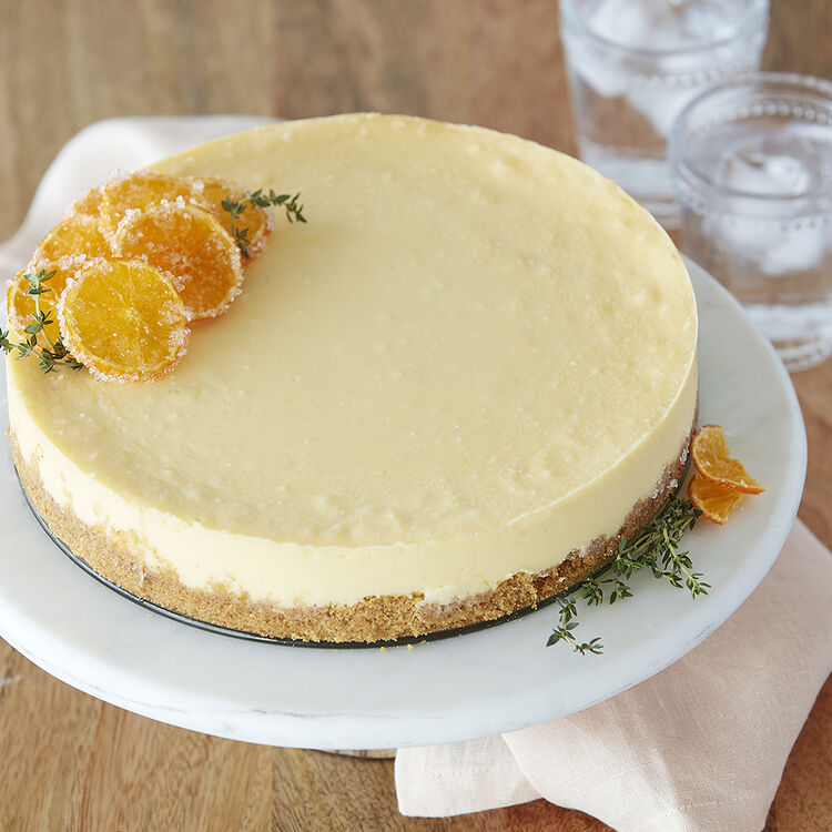 Creamy White Cheesecake topped with candied oranges