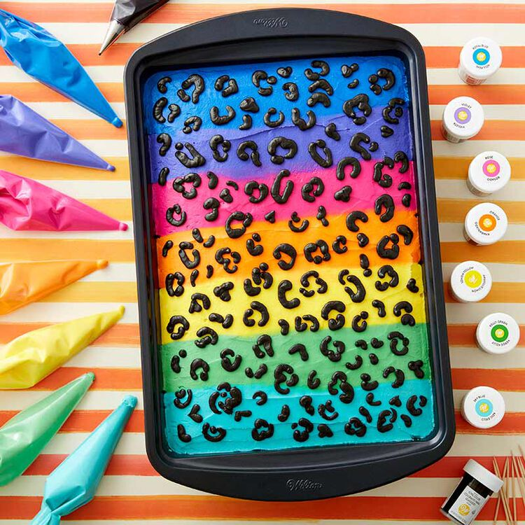Rectangular sheet cake decorated in neon colored buttercream, with animal print spots