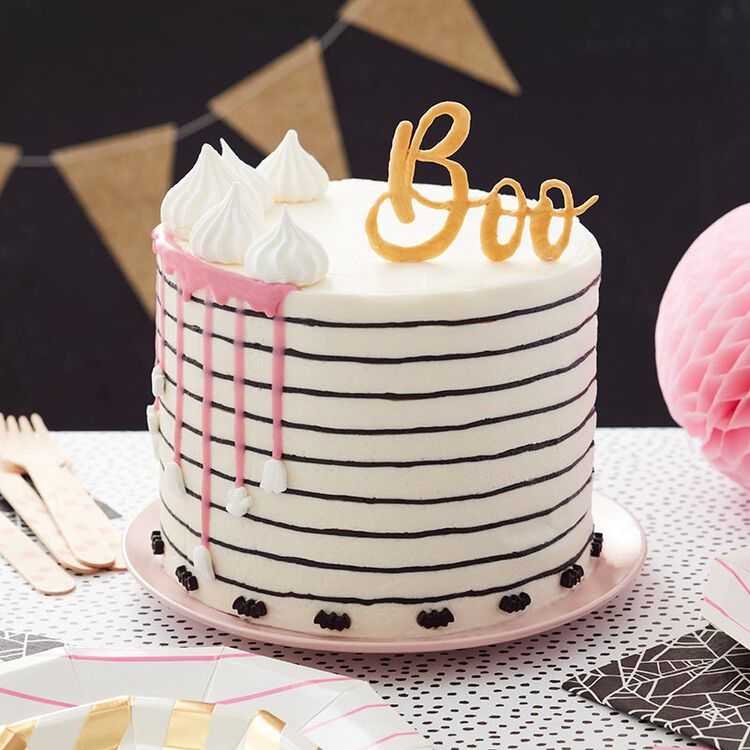 "White and pink striped cake with white ganache drips and a gold ""Boo"" Candy Melts topper"