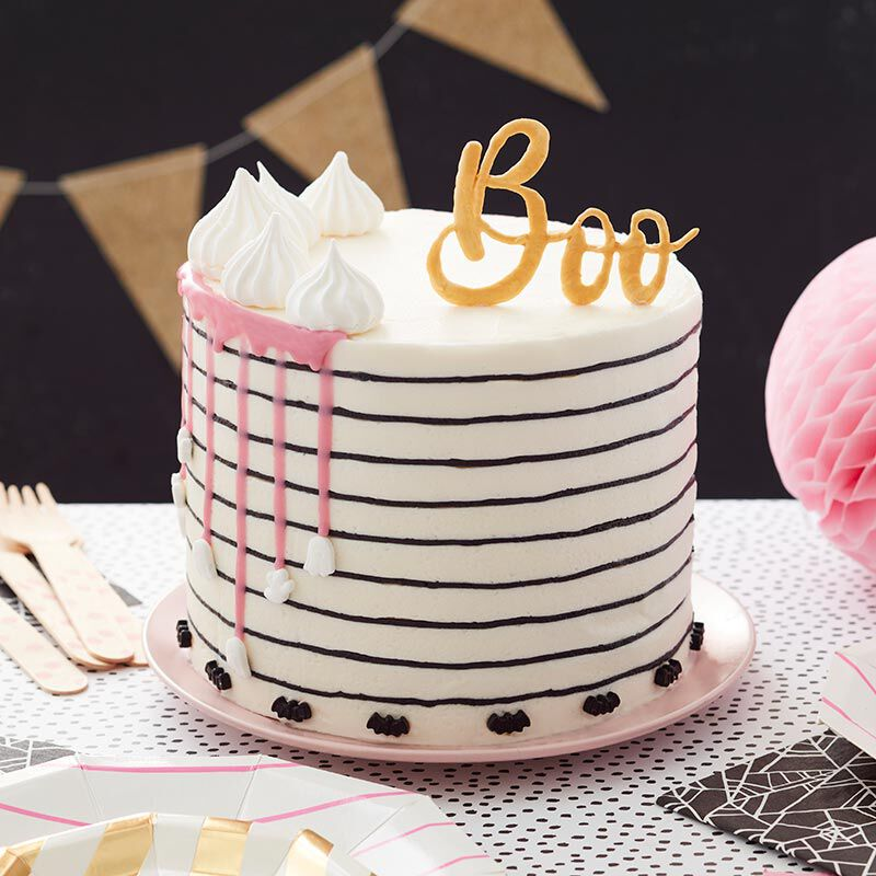 "White and pink striped cake with white ganache drips and a gold ""Boo"" Candy Melts topper image number 0"