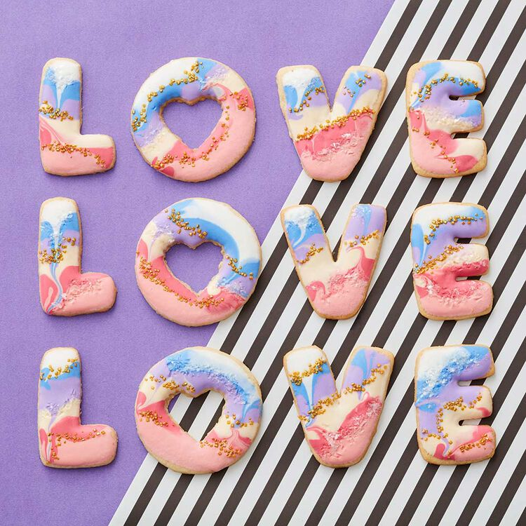 L-O-V-E cut-out cookies dipped in white, blue, red, and pink royal icing and gold sugar sprinkles