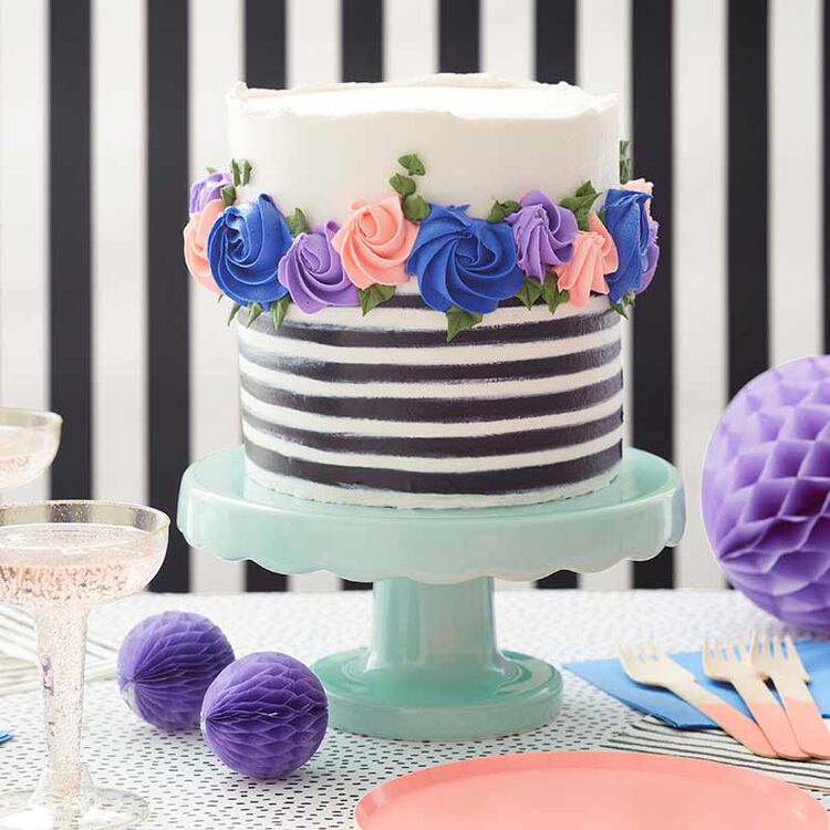 black and white striped butter cream cake decorated with purple and pink rosettes