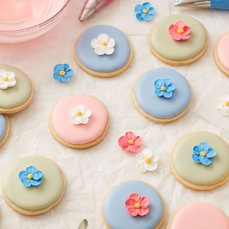 Pink, green, and blue Royal icing topped, round sugar cookies, topped with a Royal Icing forget-me-not flower