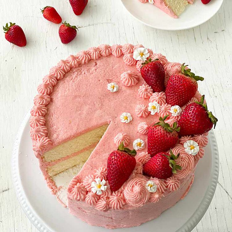 sliced vanilla cake decorated with strawberry buttercream frosting and fresh strawberries