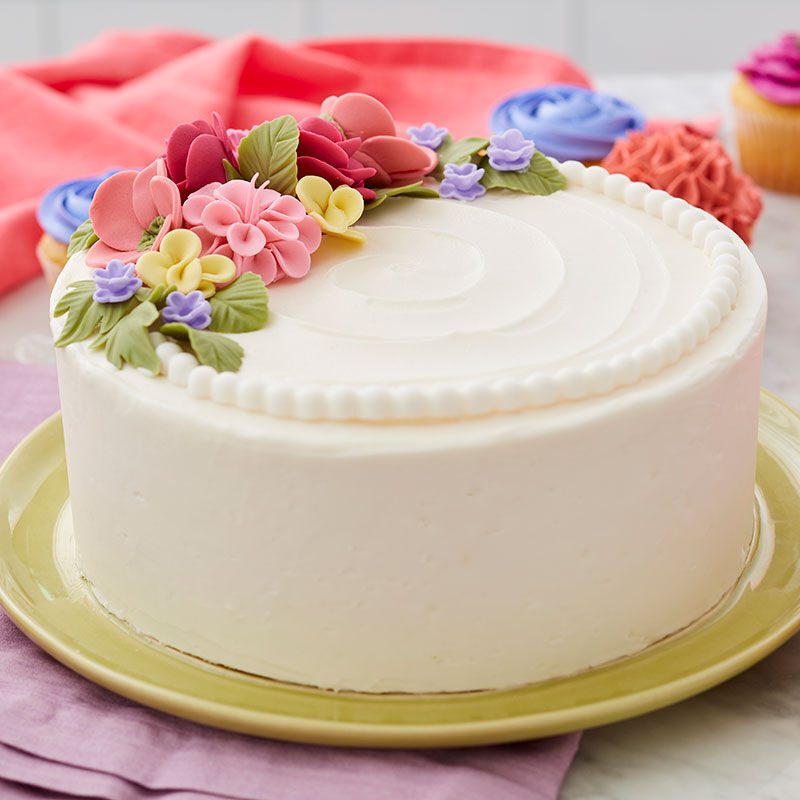 Round, white cake with different types of fondant flowers topping it. image number 2