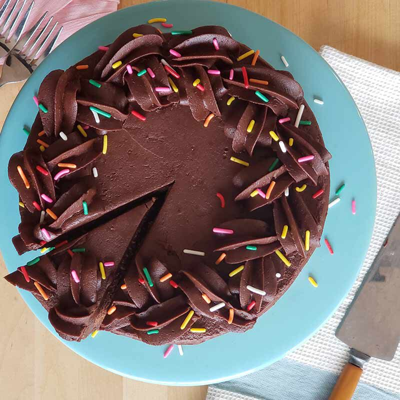slicing chocolate cake with chocolate buttercream frosting and sprinkles  image number 1