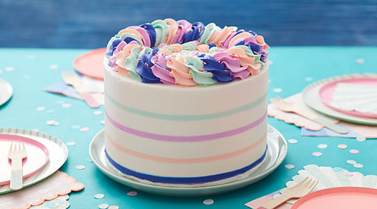 White buttercream cake decorated with blue, pink, and purple stripes around the middle and topped with buttercream