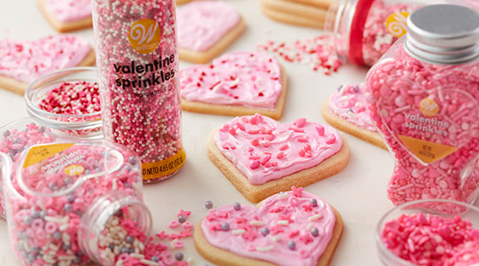 Heart-shaped cookies decorated with pink buttercream and Valentine sprinkles