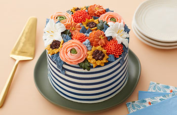 Fall buttercream flowers on top of a white and navy striped cake
