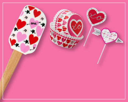 Pink background with Valentine's Day themed spatula and cupcake liners and cupcake toppers