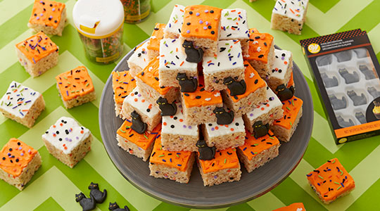 Rice crispie treats decorated with edible cat decorations and Halloween sprinkles