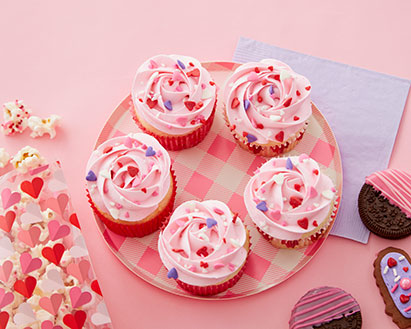 Cupcakes decorated with pink icing and cookies decorated in candy melts for Valentine's Day