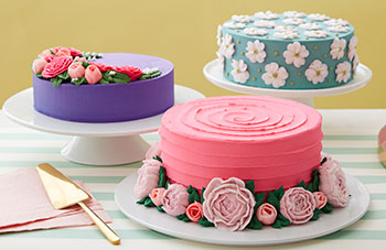 Three cakes decorated with buttercream peonies, roses, and dogwood flowers