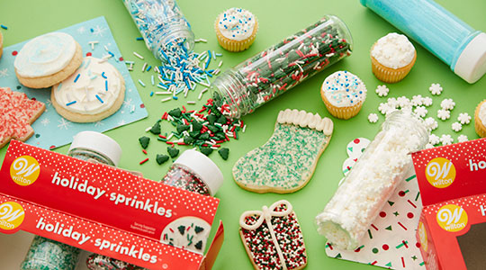 Christmas sprinkles poured out and sprinkled on Christmas-shaped cookies