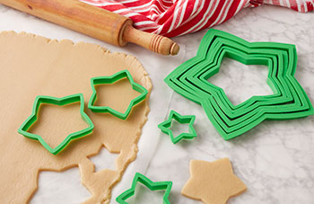 Star cookies being cut out of sugar cookie dough with star-shaped cookie cutters