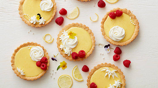 Small Lemon Tarts topped with whipped topping and raspberries.