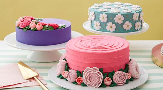 Three cakes decorated with buttercream peonies, roses, and dogwood flowers,
