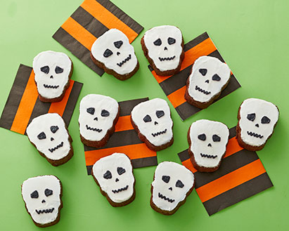 Skull-shaped brownies with white icing for the face and black icing for the eyes, nose, and mouth
