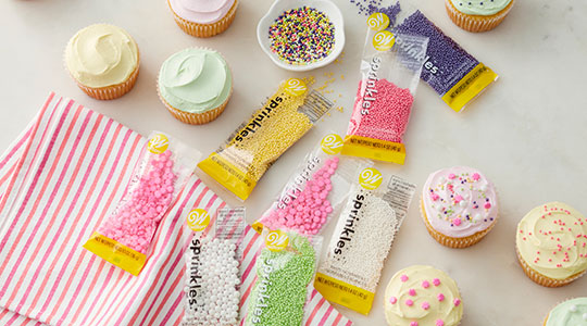 Pink, yellow, white, light green, purple sprinkle packets and cupcakes topped with sprinkles